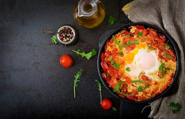 Ontbijt. gebakken eieren met groenten. shakshuka in een koekenpan op een zwarte in turkse stijl.