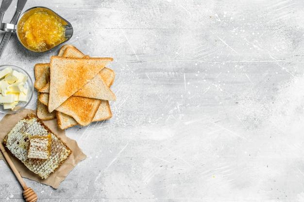 Ontbijt. geroosterd brood, honing met sinaasappeljam en boter. op een rustieke ondergrond.