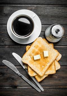 Ontbijt. geroosterd brood met boter en aromatische koffie.