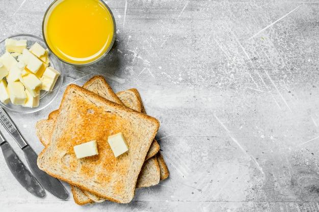 Ontbijt. geroosterd brood met boter en een glas sinaasappelsap. op een rustieke achtergrond.