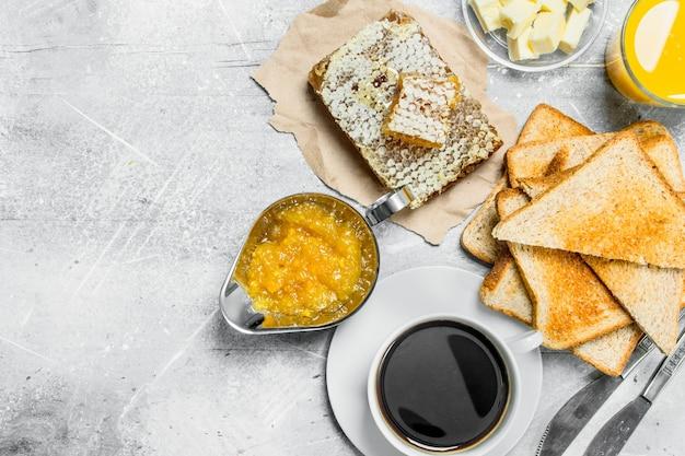 Ontbijt. geroosterd brood met boter, honing en sinaasappeljam. op een rustieke ondergrond.