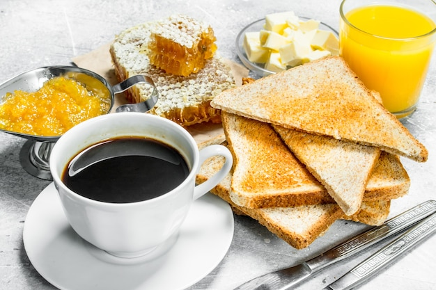 Ontbijt. geroosterd brood met boter, honing en sinaasappeljam.
