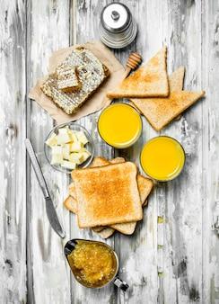 Ontbijt. geroosterd brood met boter, honing en sinaasappelsap. op houten rustiek.