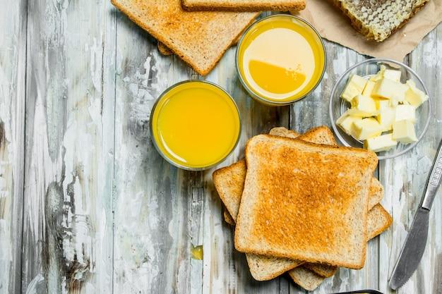 Ontbijt. geroosterd brood met boter, honing en sinaasappelsap. op houten rustieke achtergrond.