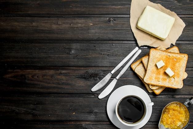 Ontbijt. geroosterd brood met boter, koffie en sinaasappeljam.