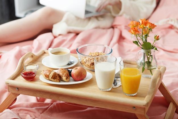 Ontbijt geserveerd in bed op houten dienblad met koffie en croissants