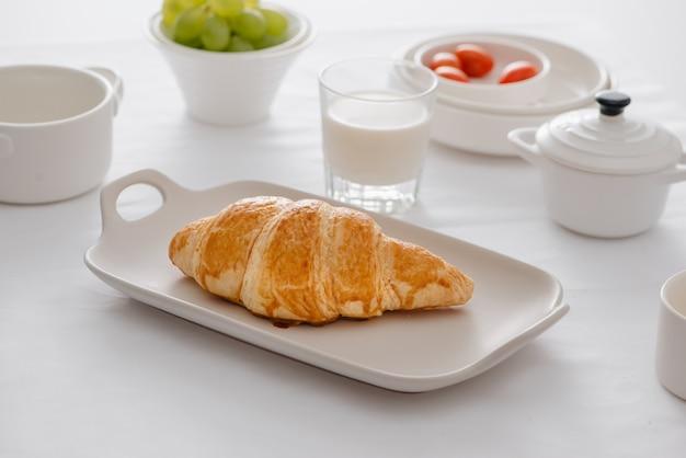 Ontbijt geserveerd met croissants, verse druiven, eieren, tomaat, melk, boter en sinaasappeljam