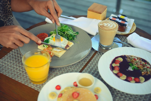 Ontbijt geserveerd met gebakken ei, koffie, jus d'orange, ontbijtgranen en fruit voor gezond.