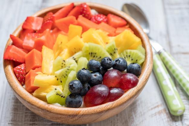 Ontbijt havermout voor kinderen gegarneerd met regenboogfruit