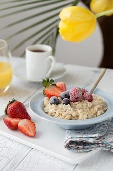 Ontbijt havermoutpap met fruit bessen en koffiekopje. havermout met aardbeien en bessen. gezond ontbijt heerlijk zelfgemaakt engels ontbijtconcept voor achtergrond.