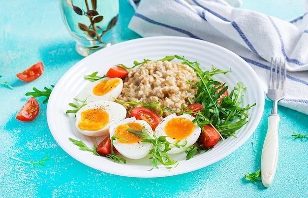 Ontbijt havermoutpap met gekookt ei, kerstomaatjes en rucola