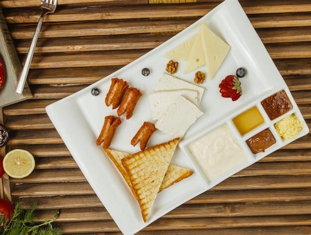 Ontbijt houten bord met pannenkoeken, honing, roomkaas, groenten en confituur in een vierkant wit bord