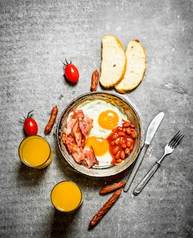 Ontbijt in de ochtend. spek, gebakken eieren met bonen en sinaasappelsap. op de stenen tafel.