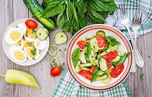 Ontbijt in de zomertuin. salade van tomaten en komkommers met groene uien en basilicum.