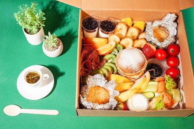 Ontbijt in een thuisbezorgdoos. lekker eten, thee, groene bloemplanten.