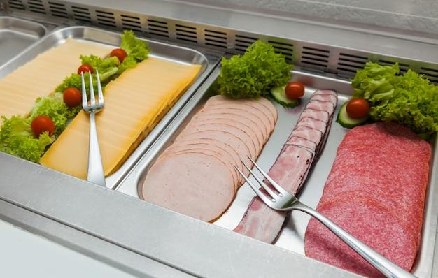 Ontbijt in het buffet van het hotel. verse groenten, worst, salami, vlees in de koelkast voor klanten.