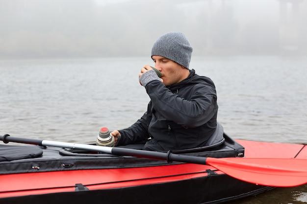Ontbijt in kano in het midden van de rivier, man genietend van warme drank uit thermoskan