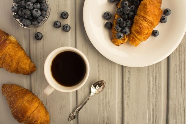 Ontbijt: koffie, croissant met pindapasta en bosbessen op de grijze houten achtergrond. bovenaanzicht. kopieer de ruimte.