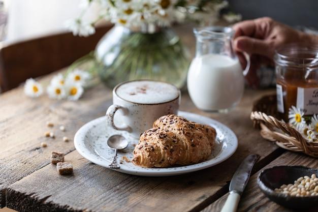 Ontbijt kopje koffie en croissant met melk en perzik of abrikozenjam op een houten tafel. boeket margrieten. rustiek