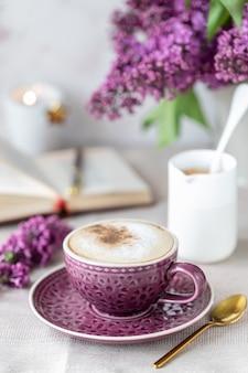 Ontbijt kopje koffie, wafels, melk en room en lila bloemen. ochtend
