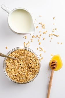 Ontbijt met atmeal vlokken, melk pot en honing beer op wit