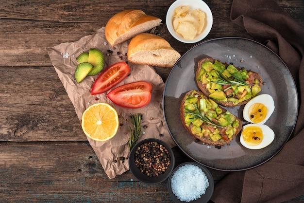 Ontbijt met avocado sandwiches op een houten achtergrond. bovenaanzicht, met ruimte om te kopiëren. het concept van goede voeding.