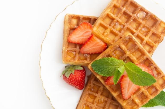 Ontbijt met belgische wafels met aardbeienmunt op bord en sinaasappelsap