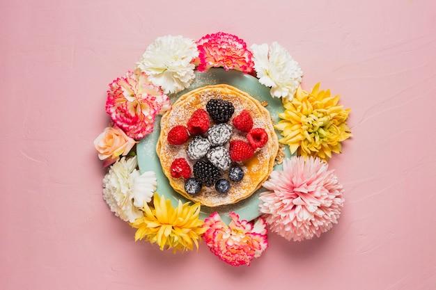 Ontbijt met bloemen en roze achtergrond