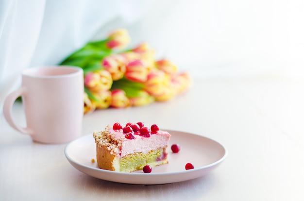 Ontbijt met bloemen tulpen, cake, thee, koffie in roze mok op lichte ondergrond.