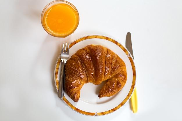Ontbijt met croissant en sinaasappelsap op gerecht