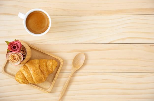 Ontbijt met croissant op een houten plaat en een kopje koffie