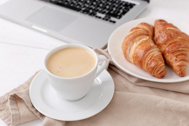 Ontbijt met croissants en koffie bij een laptop