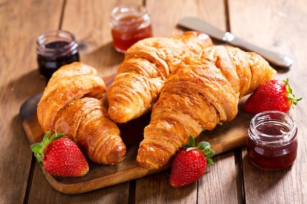 Ontbijt met croissants, jam en aardbeien op houten tafel