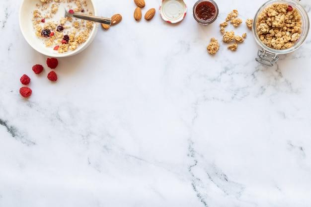 Ontbijt met crunch met rood fruit, amandelmelk en jam op marmer