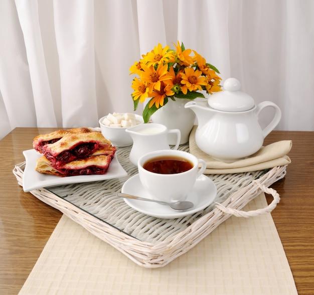 Ontbijt met de kersenstrudel met thee en melk op een dienblad