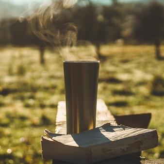 Ontbijt met een boek in de open lucht, warme deken, stoom boven een thermobeker