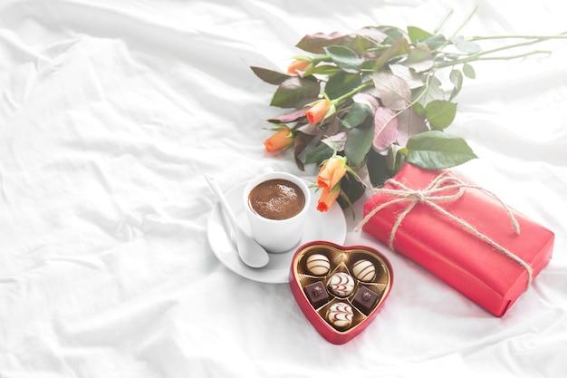 Ontbijt met een geschenk, bloemen en bonbons