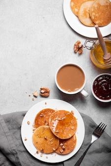 Ontbijt met een kopje koffie en kleine pannenkoekjes met honing en noten