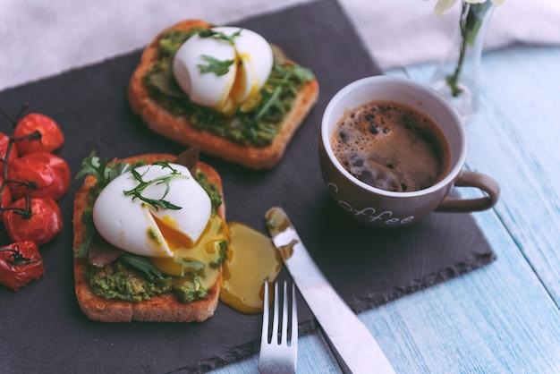 Ontbijt met ei gepocheerd op avocadopeddel en basilicum en een kopje koffie
