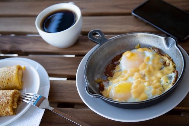Ontbijt met eieren, toast, pannenkoeken en koffie. verbrande roerei. een mager vrijgezellenontbijt, ochtend