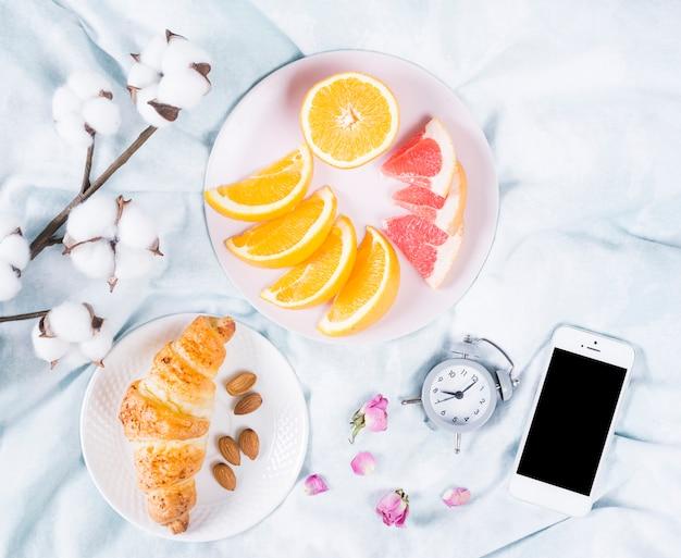 Ontbijt met fruit en mobiele telefoon