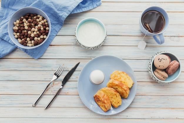 Ontbijt met gebakken croutons yoghurt en zwarte thee op licht houten oppervlak zomer landvoedsel