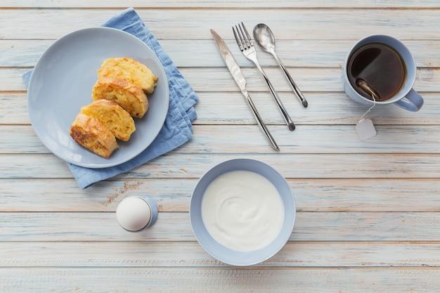 Ontbijt met gebakken croutons, yoghurt en zwarte thee op lichte houten ondergrond. zomer landvoedsel. bovenaanzicht