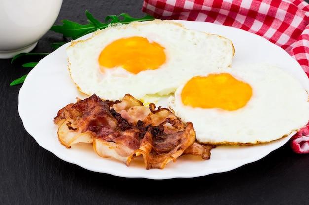 Ontbijt met gebakken eieren en spek op donkere stenen achtergrond.