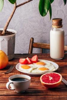 Ontbijt met gebakken eieren, koffie, plakjes tomaat en grapefruit