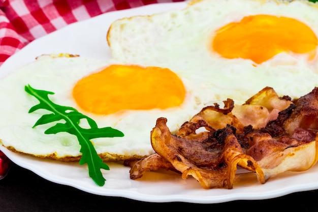 Ontbijt met gebakken eieren, spek en rucola salade op donkere stenen achtergrond.