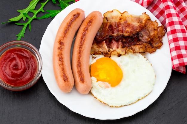 Ontbijt met gebakken eieren, spek, worstjes en groentesalade op donkere stenen achtergrond. bovenaanzicht.