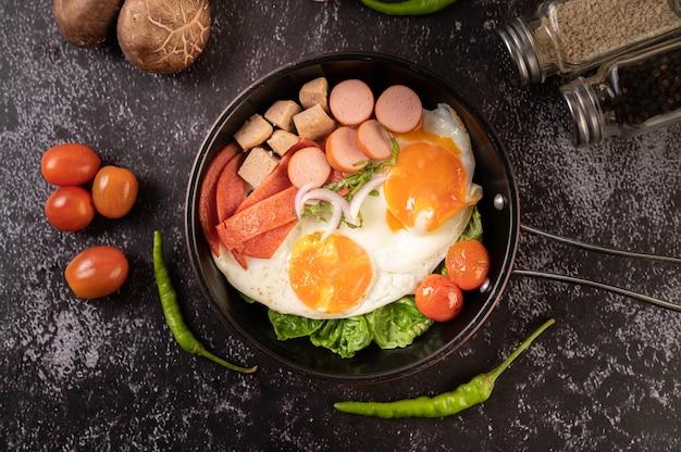 Ontbijt met gebakken eieren, worst en ham in een pan met tomaten. chili en basilicum