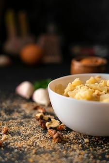 Ontbijt met geroosterde bloemkoolsalade met diverse noten in kom en groenten en eieren