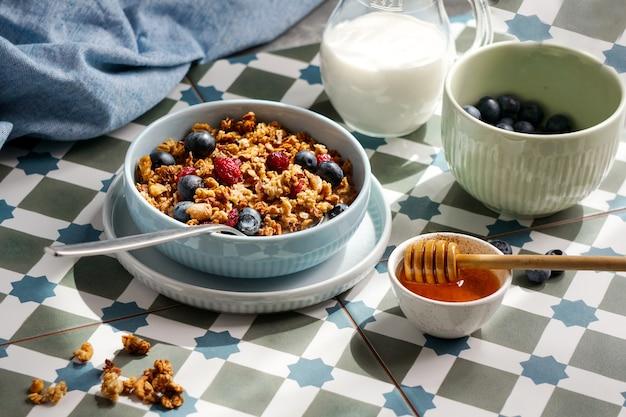 Ontbijt met granola en noten en bosbessen, honing en melk